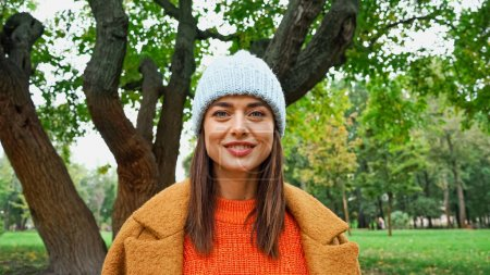 joyful woman in stylish clothes looking at camera in autumn park