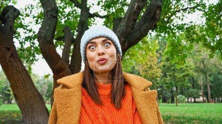 Photo pour Femme excitée avec expression folle du visage regardant la caméra dans le parc - image libre de droit