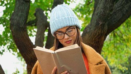 trendy woman in knitted hat and eyeglasses reading book in autumn park