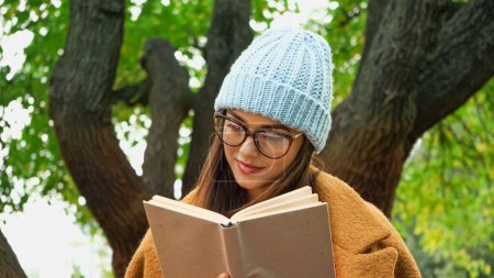 Photo for Young woman in knitted beanie and eyeglasses reading novel in park - Royalty Free Image