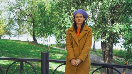 Photo for Happy woman in stylish beret and coat standing near fence in park - Royalty Free Image