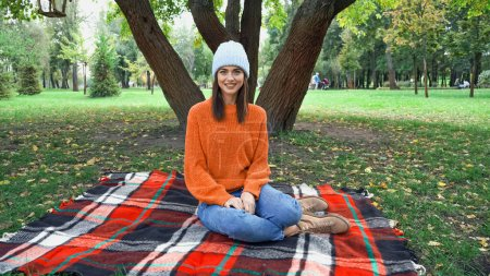Photo pour Heureuse femme élégante souriant à la caméra tout en étant assis sur une couverture à carreaux dans le parc - image libre de droit