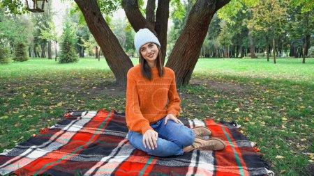 mujer alegre sonriendo a la cámara mientras descansa sobre una manta a cuadros en el parque de otoño
