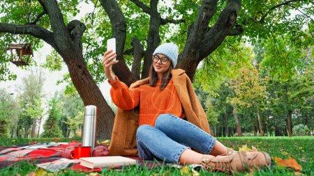 mujer sonriente en elegante traje de otoño tomando selfie en el teléfono móvil durante el picnic en el parque