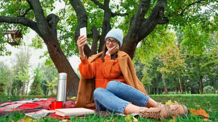 smiling woman touching face while taking selfie during picnic in park
