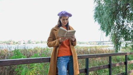 Photo pour Femme à la mode livre de lecture tout en se tenant sur le pont dans le parc d'automne - image libre de droit