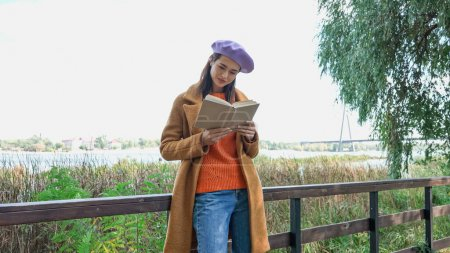 Photo for Young woman in trendy autumn clothes reading novel on bridge in park - Royalty Free Image