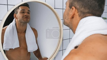 Photo for Smiling shirtless man looking at mirror in bathroom, blurred foreground - Royalty Free Image