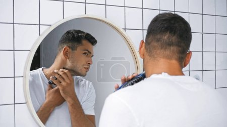 man in white t-shirt shaving neck with electric razor near mirror in bathroom