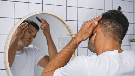 Photo pour Jeune homme brossant les cheveux avec peigne près du miroir dans la salle de bain, fond flou - image libre de droit