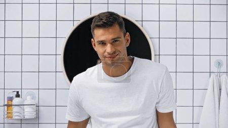 Photo pour Homme heureux en t-shirt blanc regardant caméra dans la salle de bain - image libre de droit