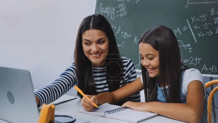 mother smiling and looking at laptop near happy daughter doing homework
