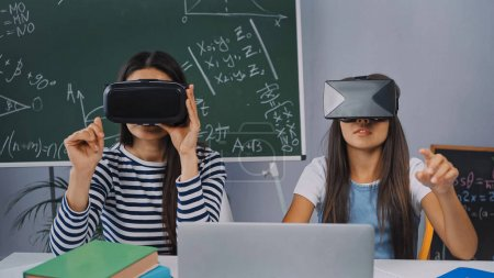 Photo for Girl gaming and pointing with finger near mother in vr headset at home - Royalty Free Image