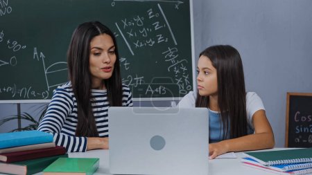 mother and daughter doing homework near laptop and notebooks on table