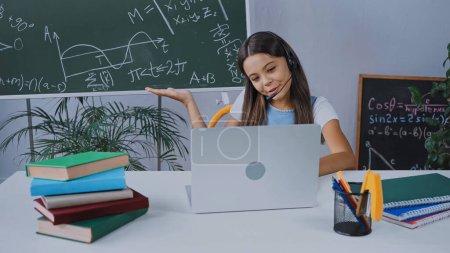 Photo pour Heureux écolier dans casque regardant ordinateur portable tout en pointant avec la main au tableau noir - image libre de droit