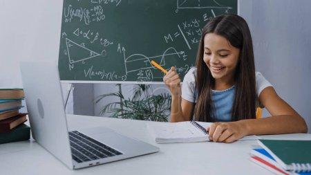 Foto de Chica feliz sosteniendo la pluma y mirando el bloc de notas cerca de la computadora portátil en el escritorio - Imagen libre de derechos