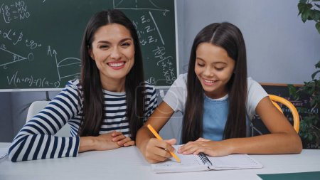 Foto de Madre sonriendo cerca feliz hija haciendo tarea en casa - Imagen libre de derechos