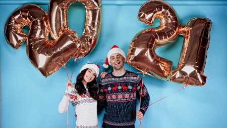 Cheerful couple in santa hats holding balloons in shape of 2021 signs on blue background