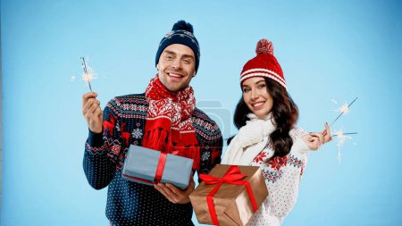 Couple in warm sweaters holding sparklers and gifts on blue background