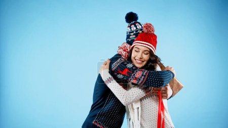 Smiling woman in hat and sweater hugging boyfriend with gift box on blue background