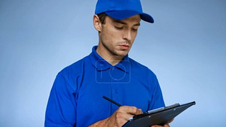 young delivery man writing on clipboard isolated on blue