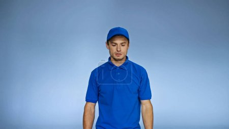 upset delivery man in uniform standing isolated on blue
