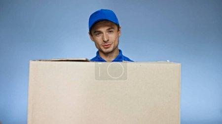 Photo pour Livreur positif regardant la caméra tout en tenant boîte en carton isolé sur bleu - image libre de droit