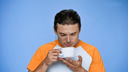 pleased man with closed eyes enjoying flavor of coffee isolated on blue