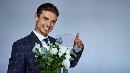 Photo pour Joyeux homme élégant pointant vers le bouquet tout en regardant loin sur le bleu - image libre de droit