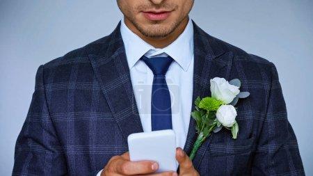 vue partielle de la messagerie souriante du marié sur téléphone portable isolé sur bleu