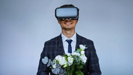 Photo for Smiling groom in vr headset holding wedding bouquet isolated on blue - Royalty Free Image