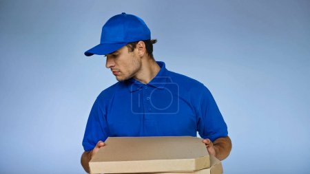 delivery man looking down while holding pizza boxes isolated on blue
