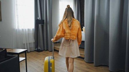 Photo pour Vue arrière de la femme en robe et veste marchant dans la chambre d'hôtel - image libre de droit