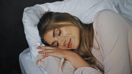 young woman with closed eyes sleeping in bed