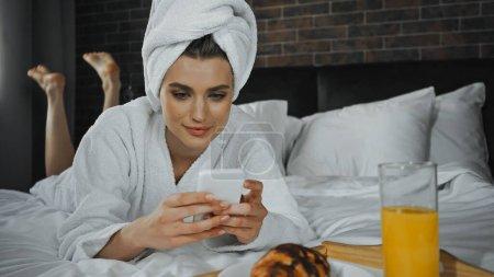 junge Frau in Handtuch mit Smartphone in der Nähe des Frühstücks auf Tablett im Hotelzimmer