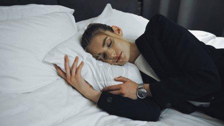 businesswoman in formal wear sleeping on bed in hotel room