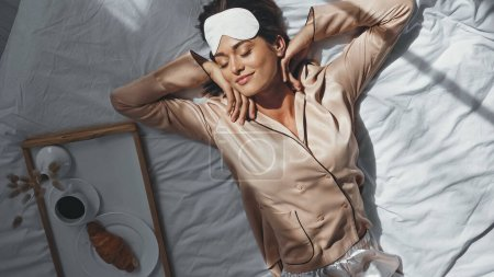 vue de dessus de la femme souriante étirant dans le lit près du plateau avec le petit déjeuner savoureux
