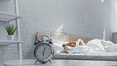 retro alarm clock near sleepy woman lying on bed in morning