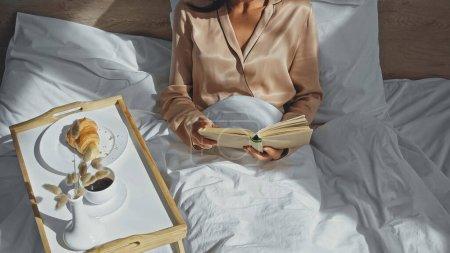 Photo pour Vue recadrée du livre de lecture femme près du plateau avec petit déjeuner savoureux - image libre de droit