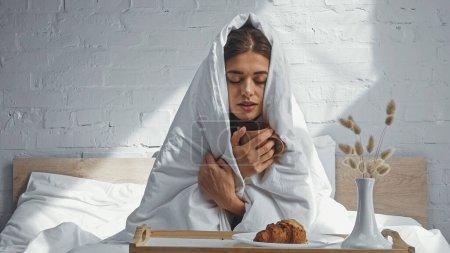Photo pour Femme gelant et tenant une tasse de thé chaud tout en étant assis sous la couverture - image libre de droit