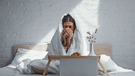Photo for Woman drinking warm tea while sitting under blanket near breakfast tray and watching movie on laptop - Royalty Free Image