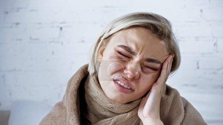 mujer enferma frunciendo el ceño con los ojos cerrados mientras sufre de dolor de cabeza en el dormitorio