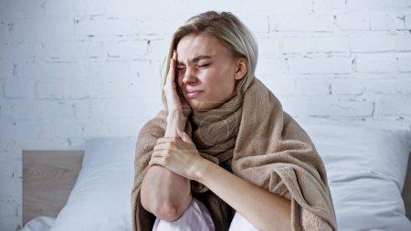 ill woman, wrapped in warm blanket, suffering from headache in bedroom