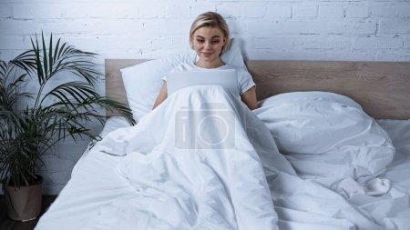 Photo pour Blogueur blonde positive en utilisant un ordinateur portable au lit - image libre de droit