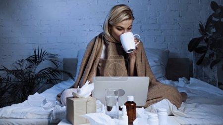 Photo pour Malade freelance boire du thé chaud près d'un ordinateur portable et des médicaments dans la chambre - image libre de droit