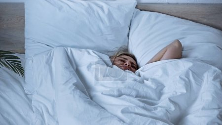 sick woman suffering from headache while lying in bed