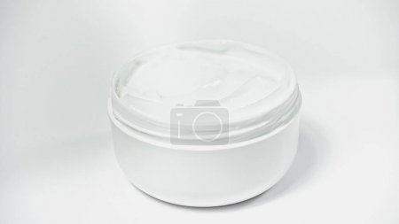jar with moisturizing cosmetic product on white