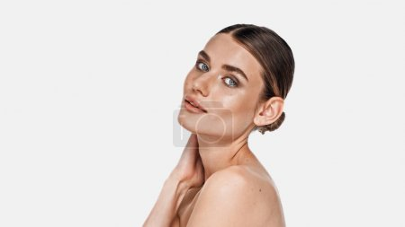 young woman with naked shoulders looking at camera isolated on white