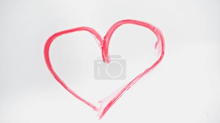 top view of drawn pink heart with lipstick on white