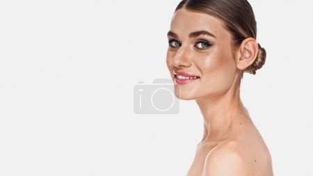 Photo for Cheerful woman with naked shoulders and makeup looking at camera isolated on white - Royalty Free Image